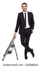 Smiling businessman leaning on stepladder on white background