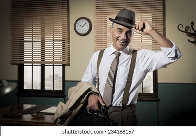 Smiling businessman leaving office holding briefcase and trench coat, 1950s style.