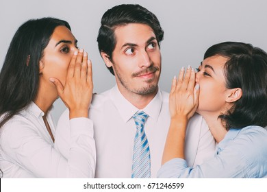 Smiling businessman listening to gossip from women