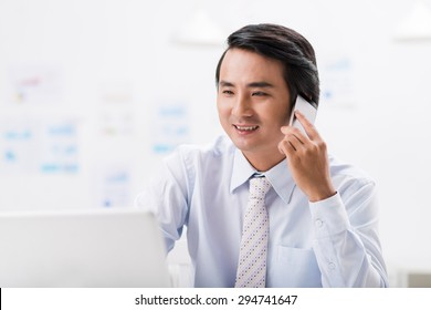 Smiling businessman looking at the laptop screen and talking on the phone