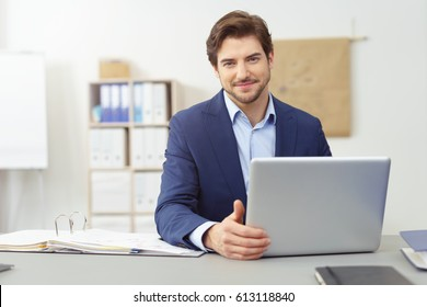 Smiling businessman looking pensively at the camera with one hand on his laptop computer as he sits at his desk