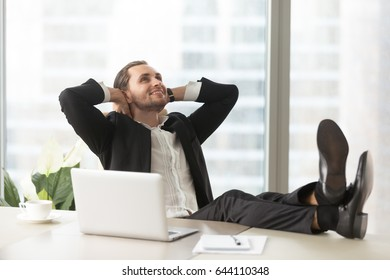 Smiling businessman looking up, sitting with legs on desk and hands behind head. Successful entrepreneur thinking about goals, tempting perspectives, happy future. Relaxing company leader enjoys work