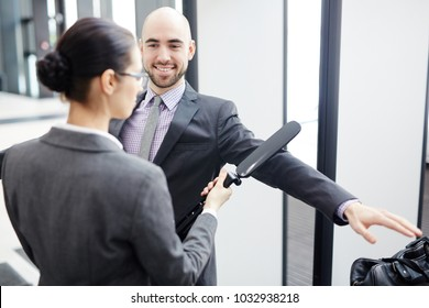 Smiling businessman looking at young airport security scanning his arm by entrance