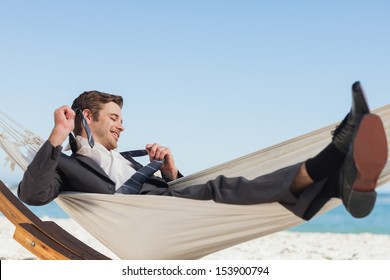 Smiling businessman lying in hammock taking off his tie at beach