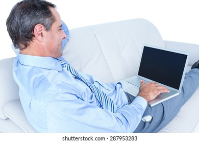 Smiling businessman lying ona sofa holding a laptop against a white wall