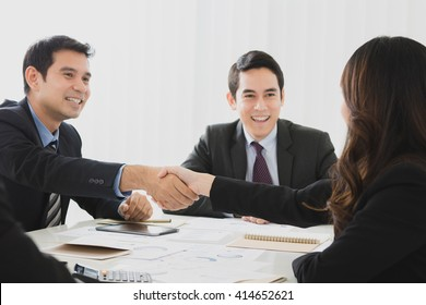 Smiling businessman making handshake with a businesswoman in the meeting