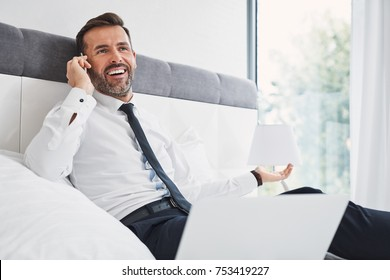 Smiling businessman making phonecall while using laptop in bedroom