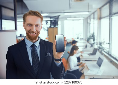 Smiling businessman manager office worker holds smartphone in hand. A man shows the display of his mobile phone