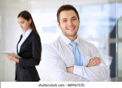 Smiling businessman  in office with colleagues in the background