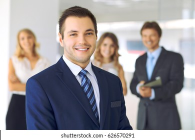 Smiling businessman  in office with colleagues in the background.