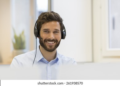 Smiling Businessman in the office on the phone, headset, Skype. looking camera