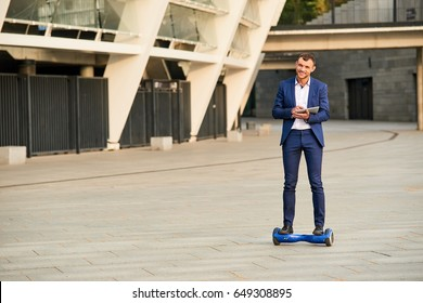 Smiling businessman on hoverboard. Happy man with tablet outdoors. Evolution of business.