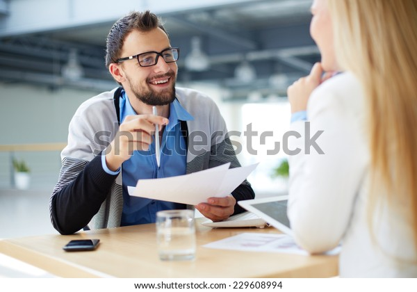 Smiling businessman with papers talking to female colleague