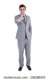 Smiling businessman pointing at the camera on white background