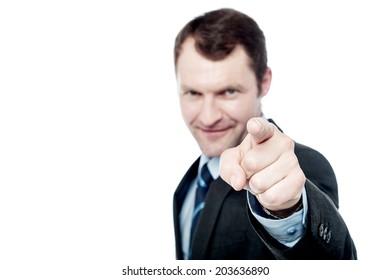Smiling businessman pointing finger at camera