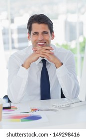 Smiling businessman posing crossing fingers in his office