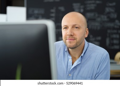 smiling businessman with an positive expression sitting at his desk in the office staring at his computer monitor