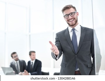 smiling businessman reaching out for a handshake