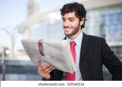 Smiling businessman reading a newspaper