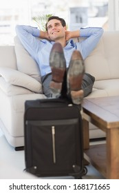 Smiling businessman relaxing on couch with feet up on suitcase in the office