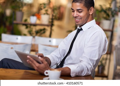 smiling businessman in the restaurant  working on ipad
