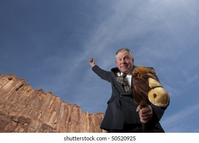 A smiling businessman rides a stick horse with one arm pointing to the sky in a desert landscape. Horizontal shot.
