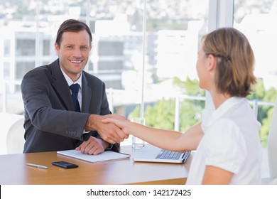 Smiling businessman shaking hand of a job applicant in his office