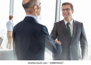 Smiling businessman shaking hands with colleague in boardroom during meeting at office