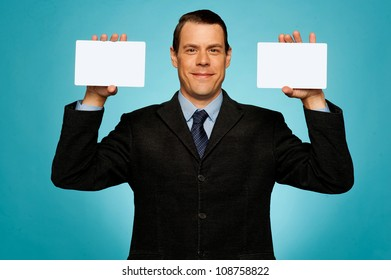 Smiling businessman showing two blank white placards to camera