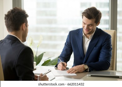 Smiling businessman signing paper at meeting, satisfied entrepreneur concludes contract, holder verifies agreement by putting authorized handwritten signature, entrepreneur making profitable deal