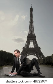 Smiling businessman sitting in front of the Eiffel Tower and working with a laptop