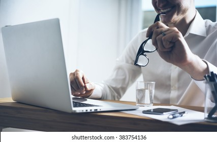 Smiling businessman sitting at his office and using laptop, holding glasses in hand, smart phone on desk, close up image of happy smiling man working on computer