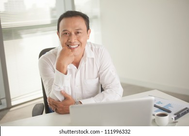 Smiling businessman sitting at his table at office