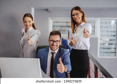 Smiling businessman sitting and showing thumbs up. Two female colleagues standing next to him and holding thumbs up. Office interior. If you do what you always did, you will get what you always got.