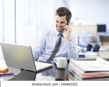 Smiling businessman sitting and using mobile phone in office