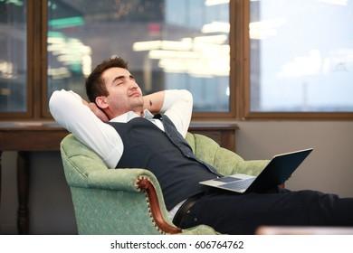 Smiling businessman sleeping in armchair with the laptopin Arlington city, Virginia.