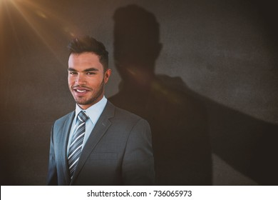 Smiling businessman standing against white background against black wall