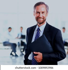Smiling businessman standing with his colleagues. Isolated on white
