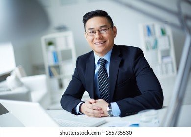 Smiling businessman in suit looking at camera in office