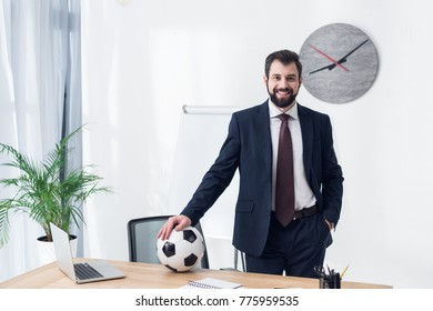 smiling businessman in suit with soccer ball at workplace in office