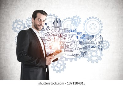 Smiling businessman with tablet standing near concrete wall with brainstorming sketch drawn on it.