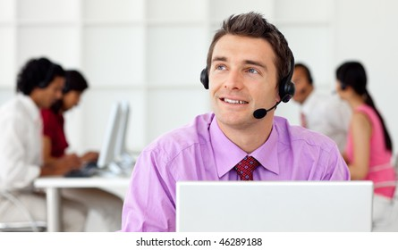 Smiling businessman talking on headset in the office