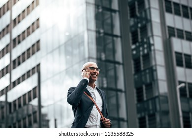 Smiling businessman talking over cell phone while commuting to office with a glass facade building in background.