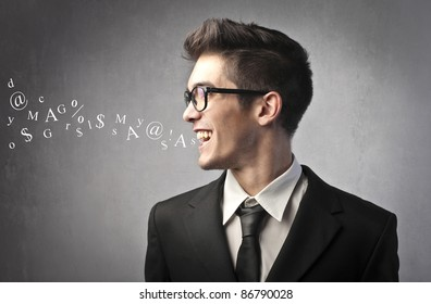 Smiling businessman talking and symbols coming out of his mouth