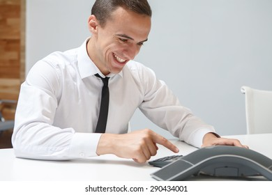 Smiling businessman talks on the conference call in the office