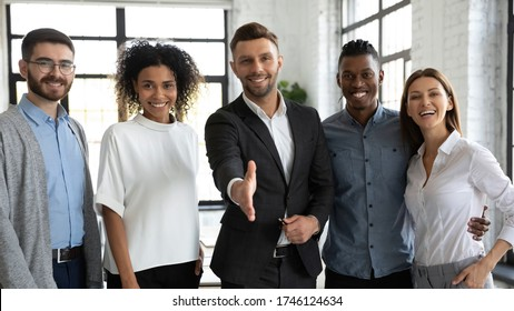 Smiling businessman team leader offering hand for handshake, standing with successful colleagues in modern office, friendly hr manager standing with extended hand, welcoming new workers at job