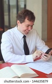 Smiling businessman typing on touchscreen