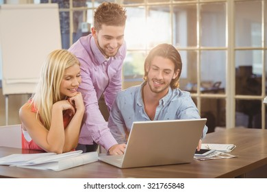 Smiling businessman using laptop while colleagues looking at it in creative office