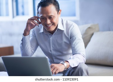 Smiling businessman using a mobile phone and looking at laptop