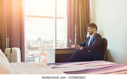 Smiling businessman using phone and drinking coffee in hotel room during business trip